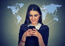 Kvinnan som använder smartphonen med över hela världen, förtjänar arkivbild