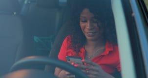 Kvinnan som använder smartphonen som sitter i bilen, överför ett meddelande arkivfilmer