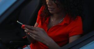 Kvinnan som använder smartphonen som sitter i bilen, överför ett meddelande stock video