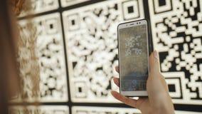 Kvinnan som använder stora QR koder för smartphonebildläsningar på den växelverkande väggen av paviljongen i ett modernt, parkera stock video