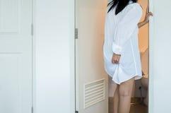 Kvinnan som använder toaletten och, lider från diarré och hemorrojder efter vak upp i morgon royaltyfria foton