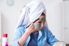 Kvinnan som applicerar leramaskeringen med den hemmastadda borsten Royaltyfria Bilder