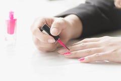 Kvinnan som applicerar rosa färger, spikar polermedel förestående Royaltyfri Foto