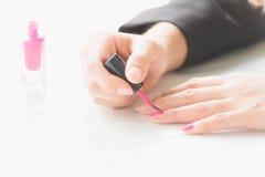 Kvinnan som applicerar rosa färger, spikar polermedel förestående Royaltyfria Bilder