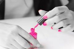 Kvinnan som applicerar rosa färger, spikar polermedel förestående Arkivbilder