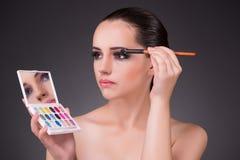Kvinnan som applicerar skuggor i skönhetbegrepp Arkivbilder