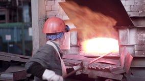 Kvinnan som arbetar med vätskesmält metall, smältte i panna på den metallurgical växten lager videofilmer