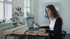 Kvinnan som arbetar vid bärbara datorn och väljer färg arkivfilmer