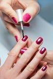 Kvinnan som att applicera spikar fernissa för att fingra, spikar Fotografering för Bildbyråer