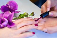 Kvinnan som att applicera spikar fernissa för att fingra, spikar Arkivbild