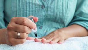 Kvinnan som att applicera spikar polermedel spikar på, för bästa lag medan hem- manikyr Kvinnapolering spikar tätt upp Hem- manik arkivfilmer