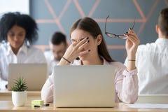 Kvinnan som av tar exponeringsglas som tröttas av arbete, ögon tröttar ut begrepp arkivfoton