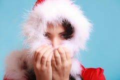 Kvinnan som bär den Santa Claus dräkten, täckte hennes framsida på blått Royaltyfri Fotografi