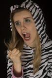 Kvinnan som bär randig kattpyjamas som visar en stängd näve, vrålar arkivfoto