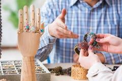 Kvinnan som besöker juveleraren för smyckenutvärdering Arkivbild