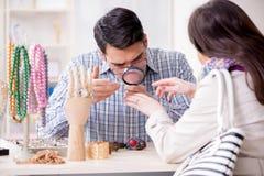 Kvinnan som besöker juveleraren för smyckenutvärdering Royaltyfri Bild