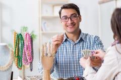 Kvinnan som besöker juveleraren för smyckenutvärdering Arkivfoto