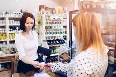 Kvinnan som betalar med kontant shoppar in Royaltyfri Fotografi