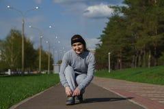 Kvinnan som binder skon, snör åt Kvinnlig sportkonditionlöpare som får klar för att jogga utomhus på skogbanan i vår eller sommar arkivfoto