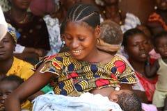 Kvinnan som breastfeeding henne, behandla som ett barn Arkivfoton