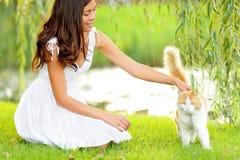 Kvinnan som daltar katten i sommar, parkerar Royaltyfri Foto