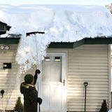 Kvinnan som drar snö av taket med snö, krattar av Arkivfoto