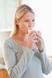Kvinnan som dricker ett exponeringsglas av, bevattnar i kök Arkivbilder