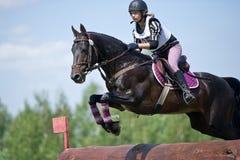 Kvinnan som eventer på häst är, övervinner journalstaketet Royaltyfri Bild