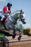 Kvinnan som eventer på häst är, övervinner Rolltopen Arkivfoton