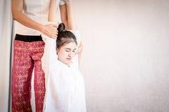 Kvinnan som får hennes arm och baksida, sträckte i thailändsk massage arkivfoto
