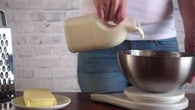 Kvinnan som förbereder omelett för frukost och häller, mjölkar in i ägg lager videofilmer