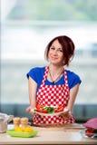 Kvinnan som förbereder sallad i köket Arkivbild