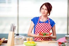 Kvinnan som förbereder sallad i köket Royaltyfri Foto