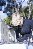 Kvinnan som förbereder sig, vindsurfar brädet Royaltyfri Fotografi