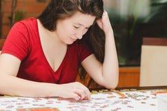 Kvinnan som försöker att matcha stycken av ett pussel, spelar Royaltyfri Bild