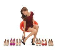 Kvinnan som försöker på höjdpunkt, heeled skor Royaltyfri Fotografi