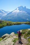 Kvinnan som fotvandrar i bergen på en turist, spårar Arkivfoton