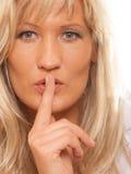 Kvinnan som frågar för tystnadfinger på kanter, hyssjar gest Fotografering för Bildbyråer