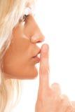Kvinnan som frågar för tystnadfinger på kanter, hyssjar gest Arkivbilder