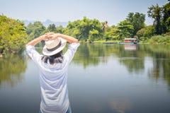 Kvinnan som framåtriktat ser till floden med för att sätta hennes händer på huvudet och henne, har känsla att koppla av och lycka royaltyfria bilder