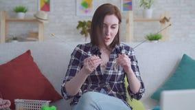 Kvinnan som framme sitter av en bärbar dator och håller ögonen på en orubblig video på att sticka, och det arbetar inte stock video