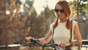 Kvinnan som går bredvid ridningcykeln på stad, parkerar Kvinnacykeln parkerar lager videofilmer