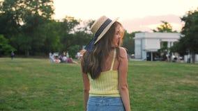 Kvinnan som går i, parkerar och ler på den ljusa sommardagen arkivfilmer