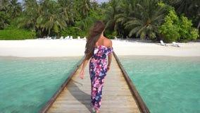 Kvinnan som går på bron på stranden med, gömma i handflatan och rent vatten av havet i Maldiverna arkivfilmer