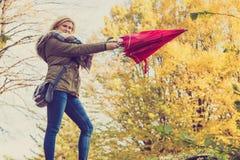 Kvinnan som in går, parkerar med paraplyet, stark vind Fotografering för Bildbyråer