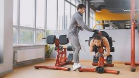 Kvinnan som gör övningar i idrottshallen - arbeta som privatlärare åt observation av utbildning Fotografering för Bildbyråer