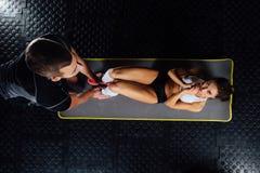 Kvinnan som gör buk- knastranden, trycker på övning på det mattt med hennes sportmaninstruktör Arkivbild