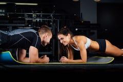 Kvinnan som gör buk- knastranden, trycker på övning på det mattt med hennes sportmaninstruktör Arkivfoton
