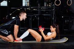 Kvinnan som gör buk- knastranden, trycker på övning på det mattt med hennes sportmaninstruktör Royaltyfri Bild