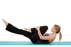 Kvinnan som gör den Pilates singeln, lägger benen på ryggen elasticitet Royaltyfri Bild